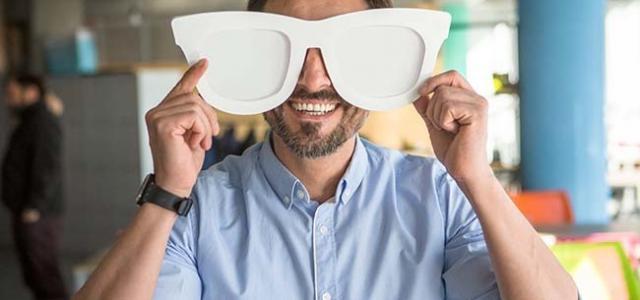 Kundenzufriedenheit aktiv steigern lachender Mann mit großer Brille Überraschung