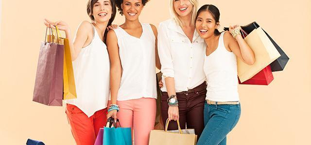 Zufriedene Kundinnen mit Einkaufstaschen in schmal